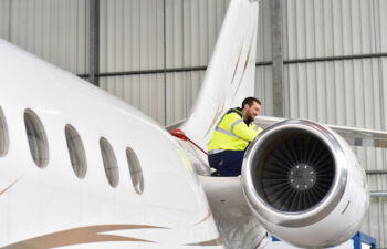 Aircraft mechanic inspects and checks the technology of a jet in a hangar at the airport